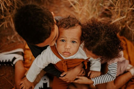 two older siblings cuddle and kiss their baby who is sitting on their lap in the spinifex grass. Baby stares up at the camera